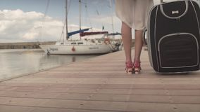 Young attractive fit woman turn back in high heels walking on wooden bridge in yacht boat harbor carrying heavy luggage. Young woman in high heels walking on stock video