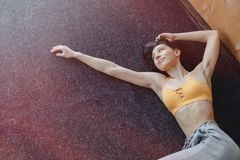 Young attractive fitness girl lying on the floor near the window on the background of a wooden wall, resting on yoga classes. At gym stock photography