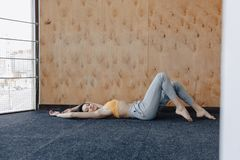 Young attractive fitness girl lying on the floor near the window on the background of a wooden wall, resting on yoga classes. At gym royalty free stock images