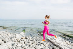 Young attractive fitness girl running on stones beach Stock Images