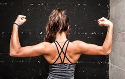 Young attractive fitness girl showing her back muscles after hard workout in the gym stock photos