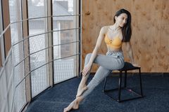 Young attractive fitness girl sitting on chair near the window on the background of a wooden wall, resting on yoga classes. At gym royalty free stock image