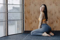 Young attractive fitness girl sitting on the floor near the window on the background of a wooden wall, resting on yoga classes. At gym royalty free stock photo
