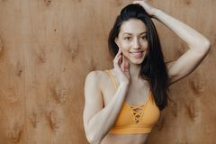 Young attractive fitness girl sitting on the floor near the window on the background of a wooden wall, resting on yoga classes. At gym stock images