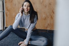 Young attractive fitness girl sitting on the floor near the window on the background of a wooden wall, resting on yoga classes and. Young attractive fitness girl stock image