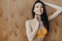 Young attractive fitness girl sitting on the floor near the window on the background of a wooden wall, resting on yoga classes. At gym royalty free stock images