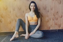 Young attractive fitness girl sitting on the floor near the window on the background of a wooden wall, resting on yoga classes. At gym royalty free stock image
