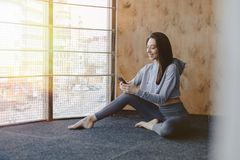 Young attractive fitness girl sitting on the floor near the window on the background of a wooden wall, resting on yoga classes and. Young attractive fitness girl royalty free stock photos