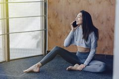 Young attractive fitness girl sitting on the floor near the window on the background of a wooden wall, resting on yoga classes and. Young attractive fitness girl stock photography