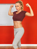 Young Attractive Fitness Woman Flexing Her Arm Muscles Wearing a Crop Top and Jogging Bottoms Stock Photos