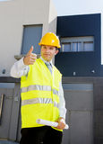 Young attractive foreman worker supervising building blueprints outdoors wearing construction helmet Stock Image