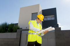 Young attractive foreman worker supervising building blueprints outdoors wearing construction helmet. And vest in housing development and real estate concept stock images