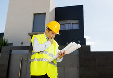 Young attractive foreman worker supervising building blueprints outdoors wearing construction helmet. And vest in housing development and real estate concept royalty free stock photos
