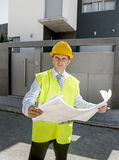 Young attractive foreman worker supervising building blueprints outdoors wearing construction helmet. And vest in housing development and real estate concept stock photo
