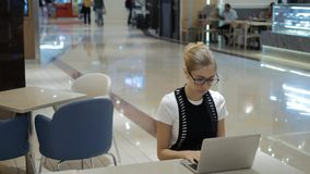 Young attractive freelancer using laptop on open space.