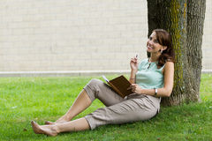 Young attractive fresh woman at the park writes in notebook jour Royalty Free Stock Image