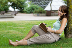 Young attractive fresh woman at the park writes in notebook jour Stock Photography