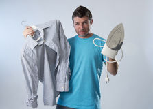 Young attractive and frustrated man holding iron and shirt stressed and tired in bored and lazy face Royalty Free Stock Image