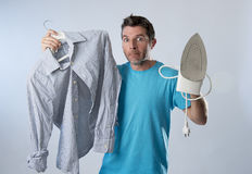Young attractive and frustrated man holding iron and shirt stressed and tired in bored and lazy face Royalty Free Stock Images