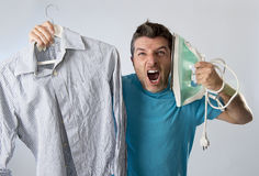 Young attractive and frustrated man holding iron and shirt stressed and tired in bored and lazy face Stock Photos