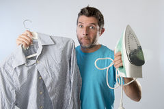 Young attractive and frustrated man holding iron and shirt stressed and tired in bored and lazy face Stock Photography