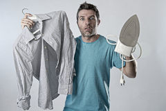 Young attractive and frustrated man holding iron and shirt stressed and tired in bored and lazy face Royalty Free Stock Photography