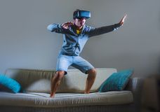Young attractive gamer man using VR goggles headgear technology playing simulator 3D video game having fun on home sofa couch enjo stock images