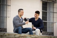 Young attractive gay men couple celebrating together Valentines day or anniversary champagne toast Stock Photo