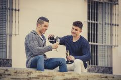 Young attractive gay men couple celebrating together Valentines day or anniversary champagne toast Stock Image