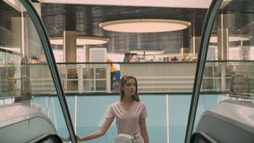 Young attractive girl appears on escalator in mall, shopping concept, fashion concept