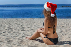 Young, attractive girl in a black bathing suit and hat of Santa on the beach by the ocean. Stock Images