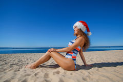 Young, attractive girl in a black bathing suit and hat of Santa Claus sitting on the beach, by the sea. Stock Photos