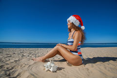 Young, attractive girl in a black bathing suit and hat of Santa Claus sitting on the beach, by the sea. Stock Images