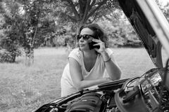 Young attractive girl with a broken car. Young girl with sunglasses, leaning on the car that broke down. She is calling for road assistance Stock Photos