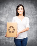 Young and attractive girl with a cardboard box Royalty Free Stock Image