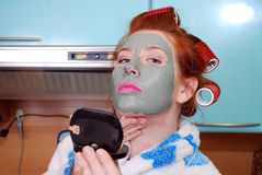 The young attractive girl in a clay mask looks in a pocket mirror Stock Photo