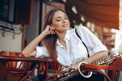 Young attractive girl with close eyes in white shirt with a saxophone sitting in caffe shop - outdoor in sity. young woman wi stock photos