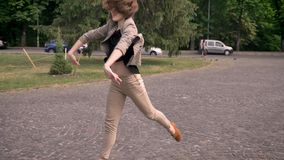 Young attractive girl is dancing in daytime, in summer, acting with hands, movement concept.  stock video footage