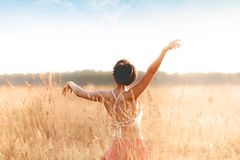 Young attractive girl dancing in field at sunset stock photography