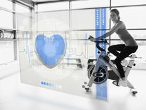 Young attractive girl doing exercise bike with futuristic interf Stock Photo