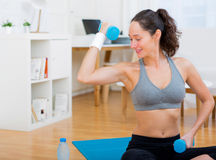 Young attractive girl doing exercise at home Stock Photos