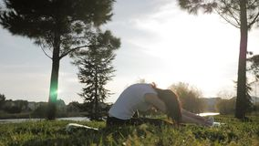 Young attractive girl doing exercises, laying and stretching on a yoga mat in park. Healthy active concept. Young attractive girl doing exercises, laying and stock footage