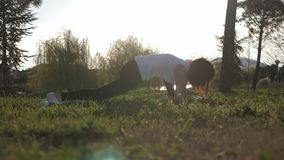 Young attractive girl doing exercises, laying and stretching on a yoga mat in park. Healthy active concept. Young attractive girl doing exercises, laying and stock video footage