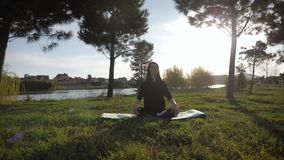 Young attractive girl doing exercises, laying and stretching on a yoga mat in park. Healthy active concept. stock video