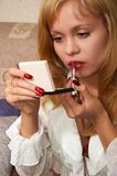 Young attractive girl doing makeup. Young attractive blonde girl in casual dress doing makeup Royalty Free Stock Photo