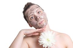 Young attractive girl doing spa facial treatment. Black mask for face. Face cleaning. Facial mask for pretty woman. Skin care. Woman with flower isolated on Royalty Free Stock Photography