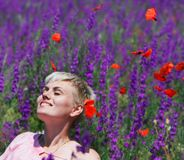 Young attractive girl dreaming in purple flowers. Red petal flying down aroung her Stock Images