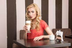 Young attractive girl drinking cappuccino. Stock Photo
