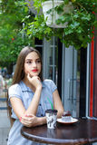 Young attractive girl drinking coffee with muffin in outdoor caf Stock Photos