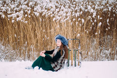 Young attractive girl embracing the snow in winter. Winter portr Royalty Free Stock Image